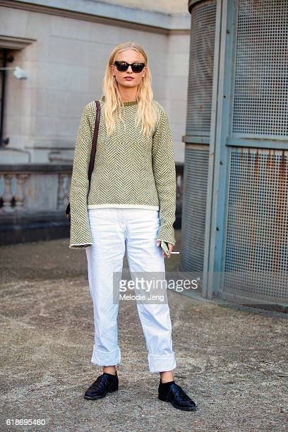 Danish model Frederikke Sofie wears green sunglasses a green knit sweater white jeans and black shoes after the Giambattista Valli show at Grand...