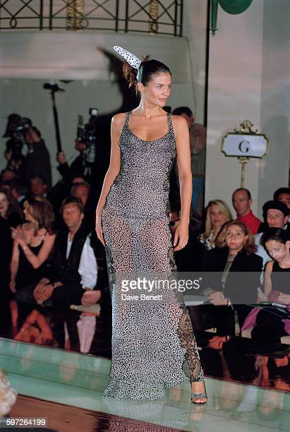 Danish model Helena Christensen wearing a full length semitransparent dress with a matching feather in her hair on the catwalk at the Gianni Versace...