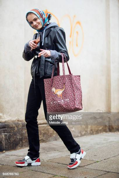 Danish model Nina Marker points at the camera and wears a scarf over her head a black belted leather jacket a red print dinosaur Coach Leatherware...