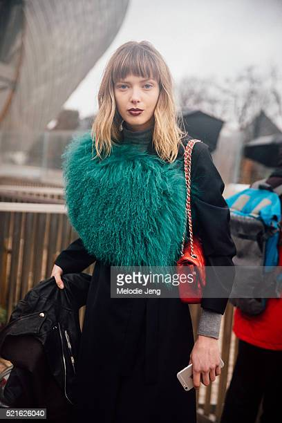 Danish model Ulrikke Hoeyer wears a green fur shawl and red Chanel purse over a black outfit after the Louis Vuitton show on Day 9 of PFW FW16 on...
