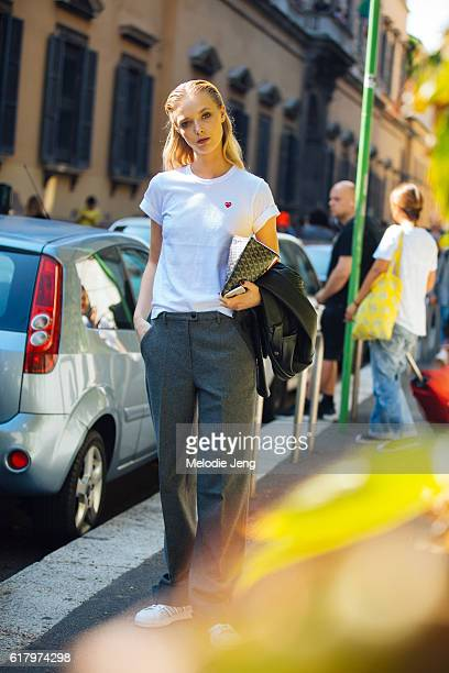 Danish model Ulrikke Hoyer wearts a white Comme des Garcons 'Play' tshirt a Goyard pouch and gray trousers after the Blumarine show during Milan...