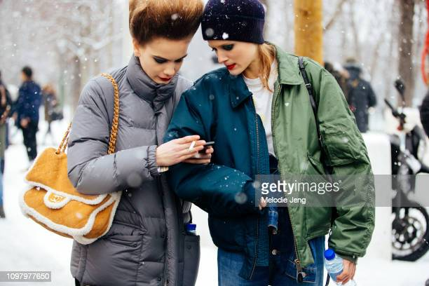 Danish models Nina Marker Sarah Dahl check their phone in the snow after the Chanel show during Couture Fashion Week Spring/Summer 2019 on January 22...