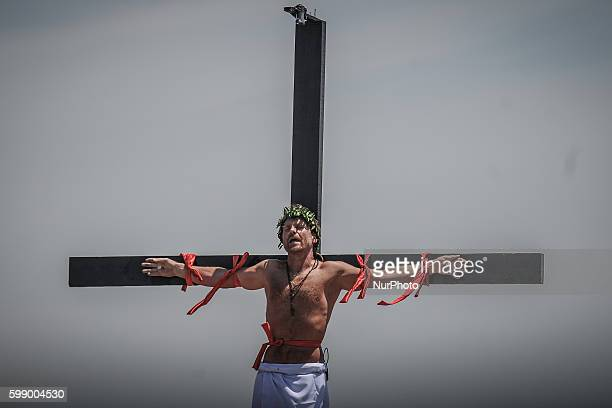 Danish national Lasse Spang Olsen a 48yearold filmmaker hangs from a wooden cross as he takes part in a crucifixion during Good Friday in San...