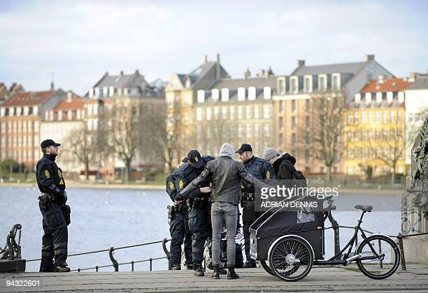 Danish police officers stop and search a potential protestor with his bicycle as he makes his way across a bridge into the centre of Copenhagen...