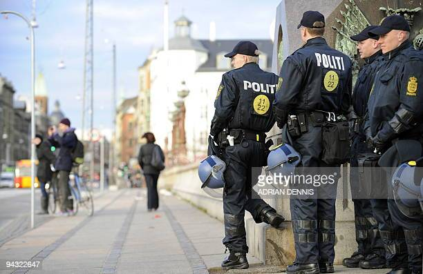 Danish police officers wait to stop and search potential protestors as they make their way across a bridge into the centre of Copenhagen December 12...