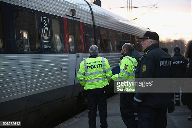 Danish policeman prepare to board a train arriving from Germany in order to check the identity papers of passengers on January 6 2016 in Padborg...