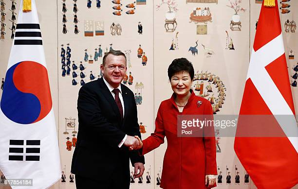 Danish Prime Minister Lars Lokke Rasmussen shakes hands with South Korean President Park Geun-Hye before their meeting at the presidential blue house...