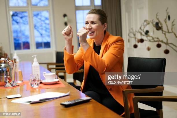 Danish Prime Minister Mette Frederiksen reacts as she follows the first innoculation via video link from her residence Marienborg, north of...