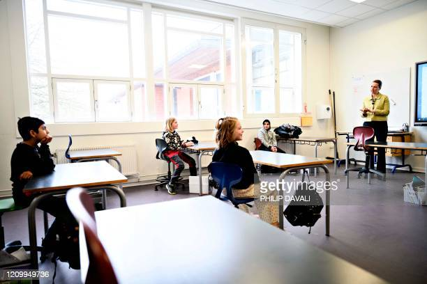 Danish Prime Minister Mette Frederiksen speaks with pupils as she participates in the reopening of Lykkebo School in Valby in Copenhagen on April 15...