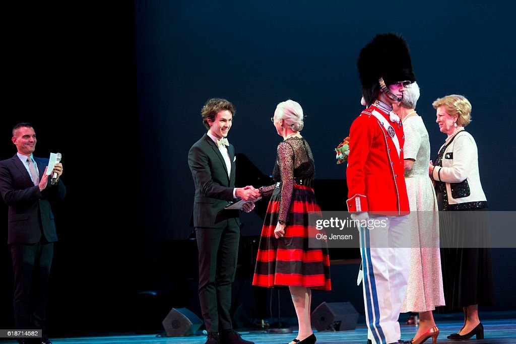 Danish Queen Margrethe (C) presents late Queen Ingrid's grant to young ballet dancer Andreas Kaas during the Alvin Ailey's American Dance Theater performance in the Tivoli Concert Hall in Copenhagen on October 27, 2016 in Denmark. The award is given every second year to two young artists within dance and music. The other award winner this year was young jazz singer Sinne Eeg.