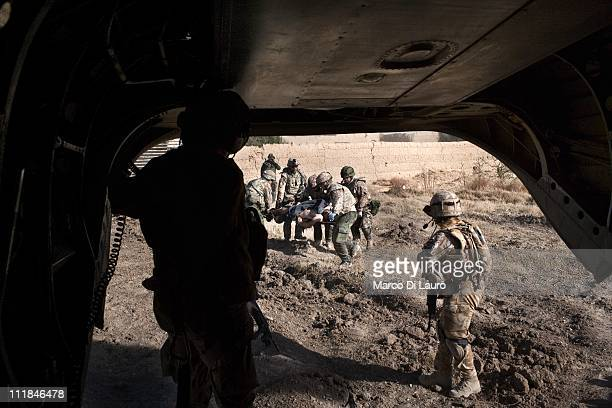 Danish soldiers carry on a stretcher into the British Royal Air Force MERT CH-47 Chinook helicopter a Danish soldier that suffered of a traumatic...