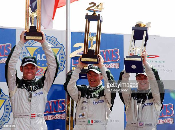 Danish Tom Kristensen Italian Rinaldo Capello and British Guy Smith driver of the Bentley holds their trophies on the podium15 June 2003 after...
