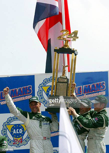 Danish Tom Kristensen Italian Rinaldo Capello and British Guy Smith driver of the Bentley hold their trophy on the podium15 June 2003 after winning...