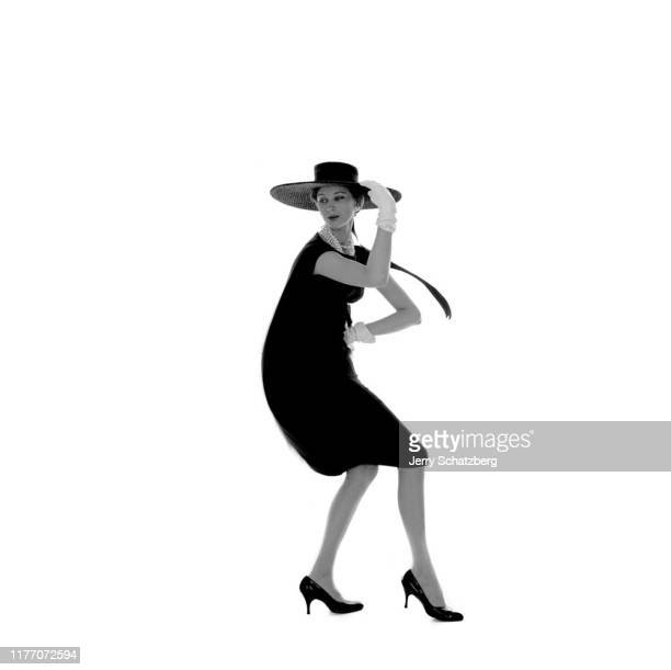 Danishborn French fashion model and actress Anna Karina in a black dress and widebrimmed hat dances against a white background New York New York...
