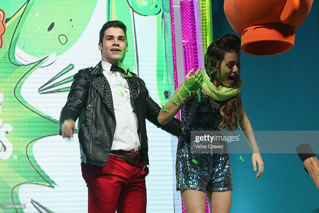 Danna Paola (R) speaks onstage after getting slimed during the Kids Choice Awards Mexico 2013 at Pepsi Center WTC on August 31, 2013 in Mexico City, Mexico.