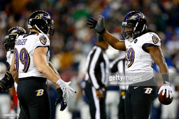 Dannell Ellerbe of the Baltimore Ravens celebrates with teammate Paul Kruger after intercepting a pass by Tom Brady of the New England Patriots in...
