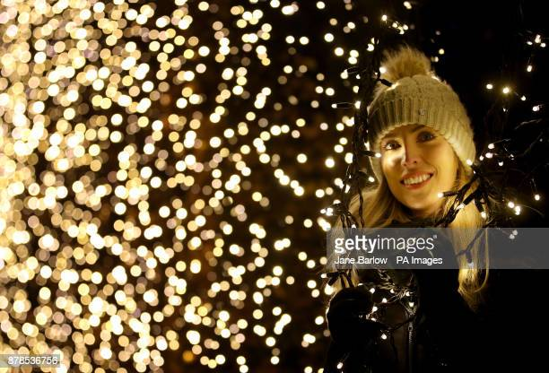 Dannielle McAllister looks through a beech hedge covered in fairy lights which is one of a series of light installations that feature in Christmas at...