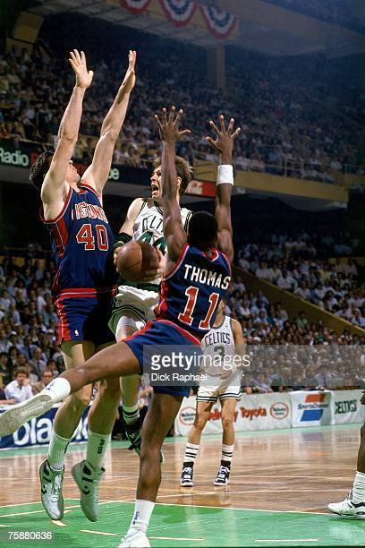 Danny Ainge of the Boston Celtics drives to the basket against Isiah Thomas and Bill Lambier of the Detroit Pistons during an NBA game circa...
