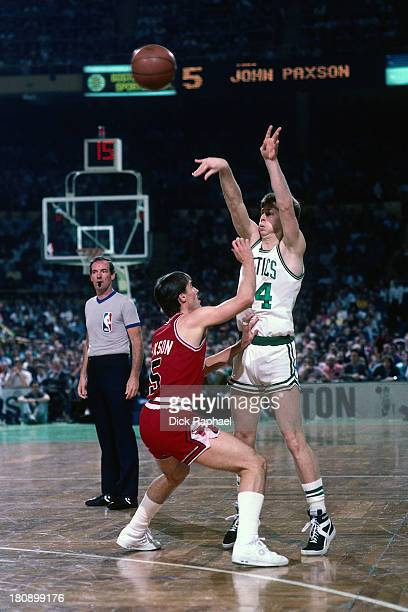 Danny Ainge of the Boston Celtics passes the ball while defended by John Paxson of the Chicago Bulls during a game circa 1986 at the Boston Garden in...