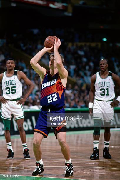 Danny Ainge of the Phoenix Suns attempts a free throw as Reggie Lewis and Xavier McDaniel of the Boston Celtics look on during a game played at the...