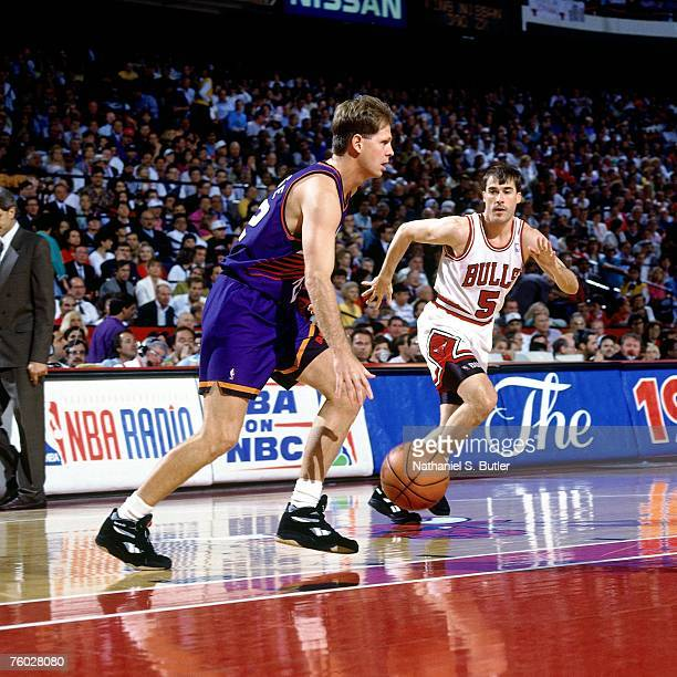 Danny Ainge of the Phoenix Suns dribbles up court against John Paxson of the Chicago Bulls in Game Four of the 1993 NBA Finals on June 16 1993 at the...
