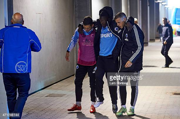 Danny Amankwaa of FC Copenhagen is carried out injured supported by two team mates during halftime in the Danish Alka Superliga match between Randers...