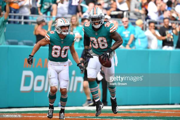 Danny Amendola and Brandon Bolden of the Miami Dolphins celebrate a touchdown against the New England Patriots at Hard Rock Stadium on December 9...