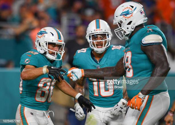 Danny Amendola Kenny Stills and Laremy Tunsil of the Miami Dolphins celebrate a touchdown in the second quarter during a preseason game against the...