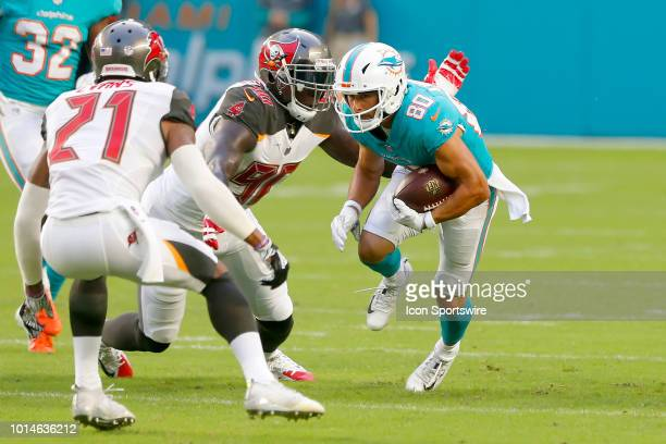 Danny Amendola of the Dolphins is wrapped up by Jason PierrePaul of the Bucs as Justin Evans looks on during the preseason game between the Tampa Bay...