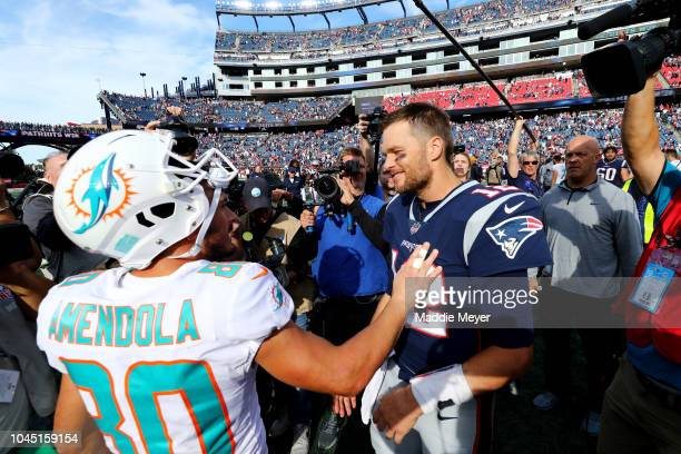 Danny Amendola of the Miami Dolphins and Tom Brady of the New England Patriots talk after the game at Gillette Stadium on September 30 2018 in...