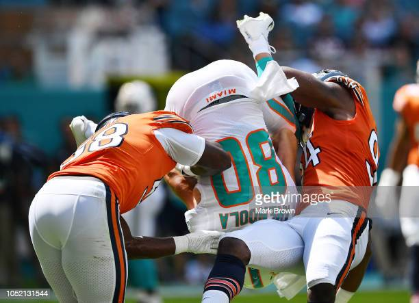 Danny Amendola of the Miami Dolphins is flipped by Leonard Floyd and Roquan Smith of the Chicago Bears in the first quarter of the game at Hard Rock...