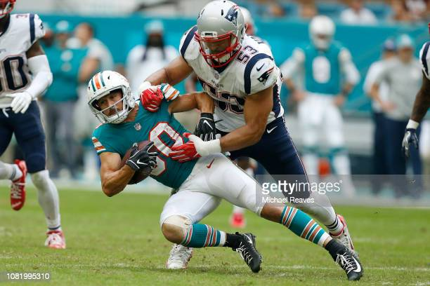 Danny Amendola of the Miami Dolphins is tackled by Kyle Van Noy of the New England Patriots at Hard Rock Stadium on December 9 2018 in Miami Florida