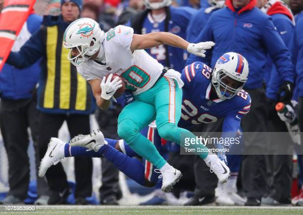 Danny Amendola of the Miami Dolphins returns a punt in the second quarter during NFL game action as he is tackled by Siran Neal of the Buffalo Bills...