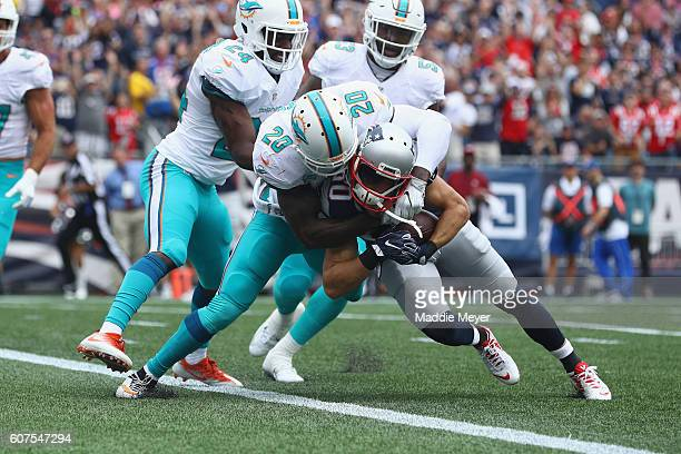 Danny Amendola of the New England Patriots scores a touchdown during the first quarter as Reshad Jones of the Miami Dolphins attempts to tackle him...