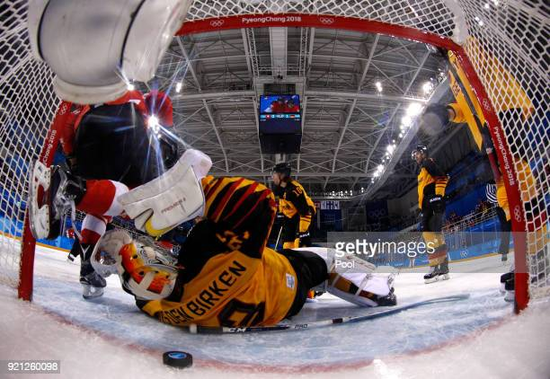 Danny Aus Den Birken of Germany lies on the ice after giving up a goal to Simon Moser of Switzerland as Andres Ambuhl of Switzerland climbs out of...