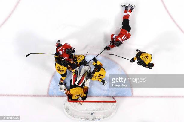 Danny Aus Den Birken of Germany makes a save against Raphael Diaz and Denis Hollenstein of Switzerland in the first period during the Men's Ice...