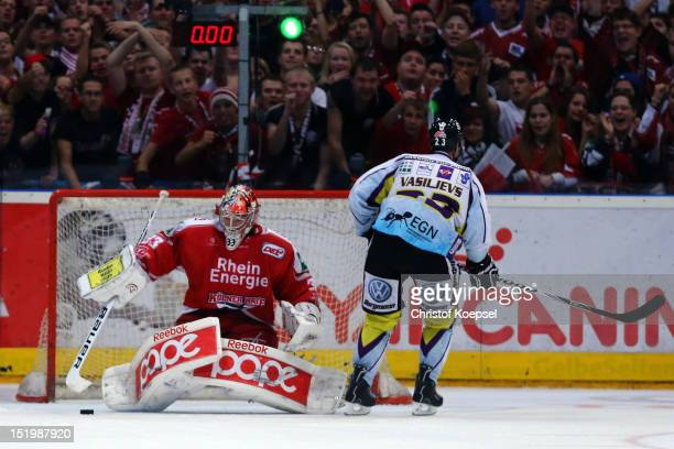 Danny aus den Birken of Koelner Haie saves a penalty against Herberts Vasilijevs of Krefeld Pinguine during the DEL match between Koelner Haie and...