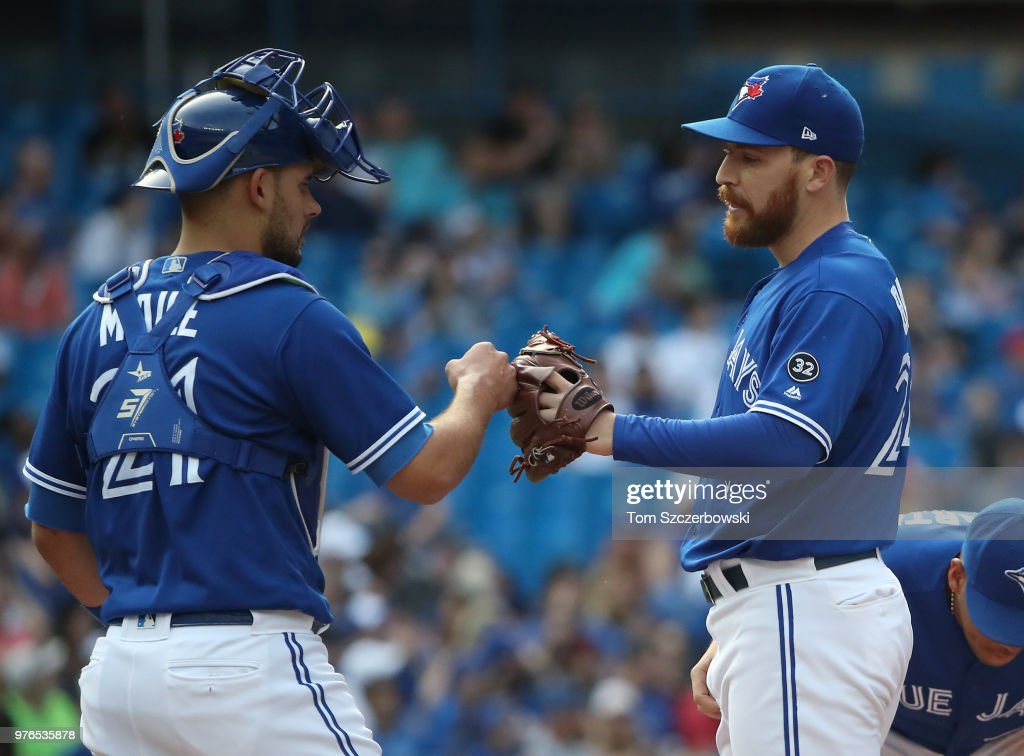 Danny Barnes #24 of the Toronto Blue Jays is congratulated by Luke Maile #21 moments before being relieved after retiring both batters he faced in the eighth inning during MLB game action against the Washington Nationals at Rogers Centre on June 16, 2018 in Toronto, Canada.