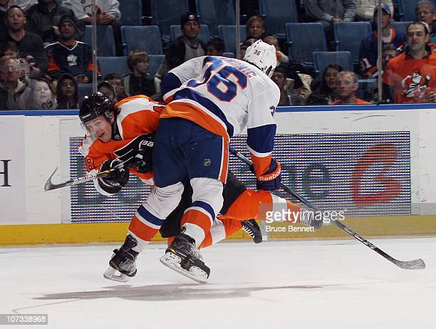Danny Briere of the Philadelphia Flyers gets off a shot as he is hit by Travis Hamonic of the New York Islanders at the Nassau Coliseum on December 5...