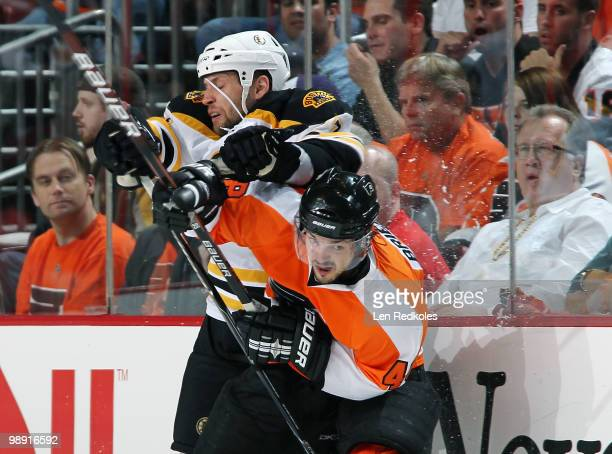 Danny Briere of the Philadelphia Flyers takes a hit along the boards from Steve Begin of the Boston Bruins in Game Four of the Eastern Conference...