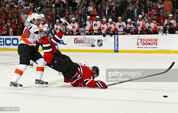 Danny Briere of the Philadelphia Flyers trips up Dainius Zubrus of the New Jersey Devils as he scores an empty net goal at 1915 of the third period...