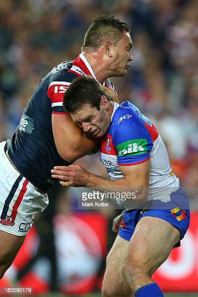 Danny Buderus of the Knights tackles Jared WaereaHargreaves of the Roosters during the NRL Preliminary Final match between the Sydney Roosters and...