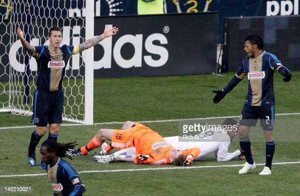 Danny Califf and Carlos Valdes of the Philadelphia Union attempt to get the attention of the referee as their goalkeeper Zac MacMath lies on the...