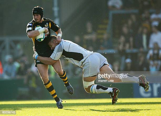 Danny Cipriani of London Wasps is tackled by Gideon Lensing of Castres Olympique during the Heineken Cup match between London Wasps and Castres...