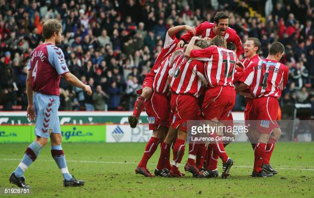 Danny Cullip of Sheffield United is mobbed after scoring the equalising goal during the FA Cup Third Round match between Sheffield United and Aston...