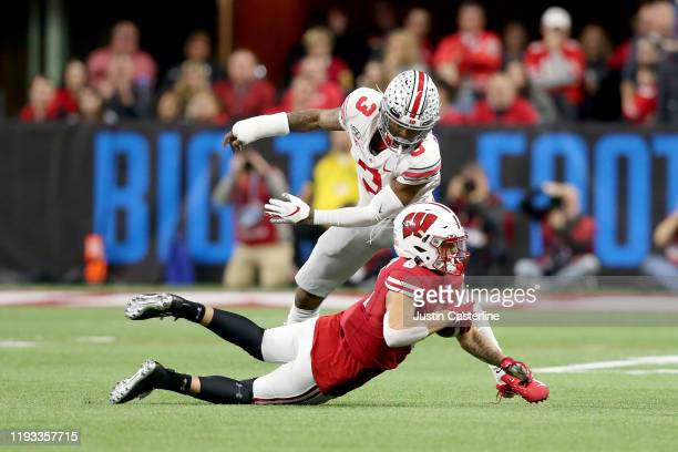 Danny Davis III of the Wisconsin Badgers catches a pass while being defended by Damon Arnette of the Ohio State Buckeyes in the Big Ten Championship...