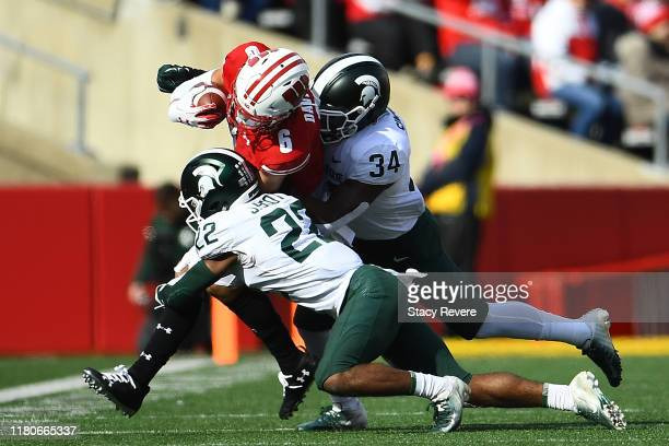 Danny Davis III of the Wisconsin Badgers is brought down by Josiah Scott and Antjuan Simmons of the Michigan State Spartans during the first half at...