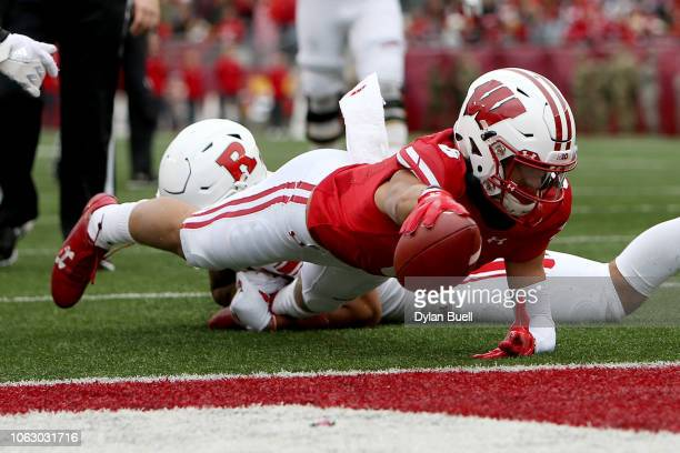 Danny Davis III of the Wisconsin Badgers scores a touchdown past Isaiah Wharton of the Rutgers Scarlet Knights in the fourth quarter at Camp Randall...