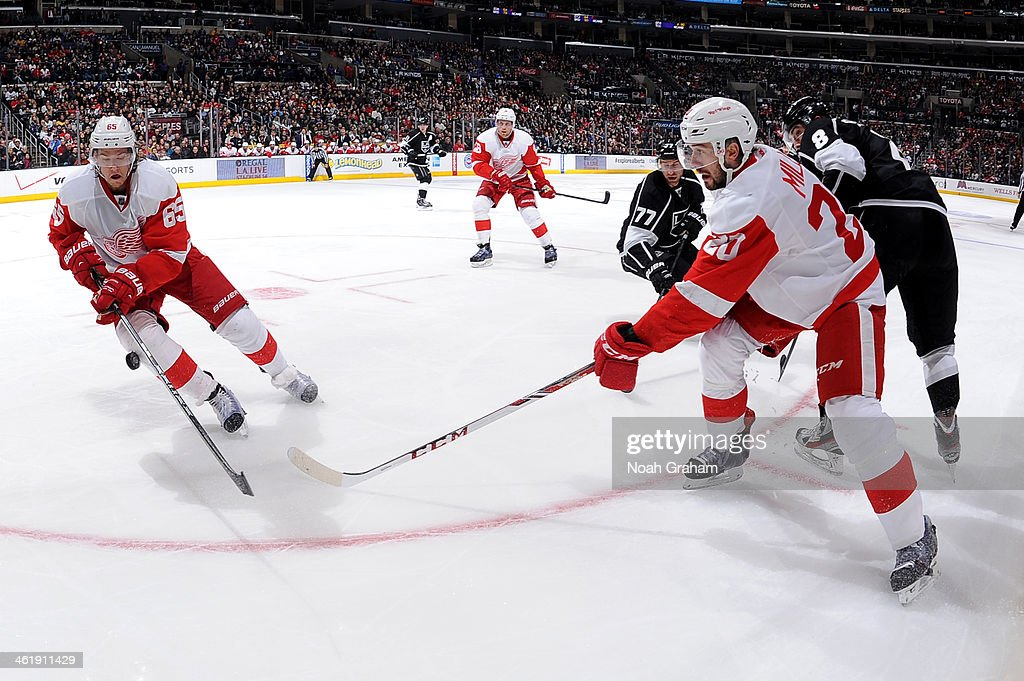 Danny DeKeyser #65 and Drew Miller #20 of of the Detroit Red Wings reach for the puck against the Los Angeles Kings at Staples Center on January 11, 2014 in Los Angeles, California.