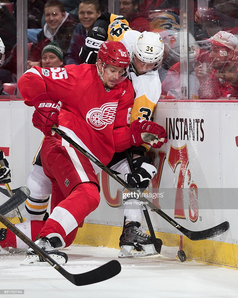 Danny DeKeyser #65 of the Detroit Red Wings battles along the boards for the puck with Tom Kuhnhackl #34 of the Pittsburgh Penguins during an NHL game at Joe Louis Arena on January 14, 2017 in Detroit, Michigan.